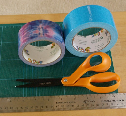 Duck® Tape, FISKARS® scissors with non-stick Teflon® blades, ruler, craft mat. Totally Tie-Dye Duck Tape® is on the left, and Electric Blue Duck Tape® is on the right.