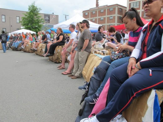 Crowd Sitting on Recycled Paper Bales