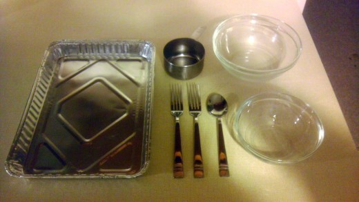 Gather hardware: a cup measure, two forks, a spoon, two baking pans, two bowls, and a pasta pot and strainer.