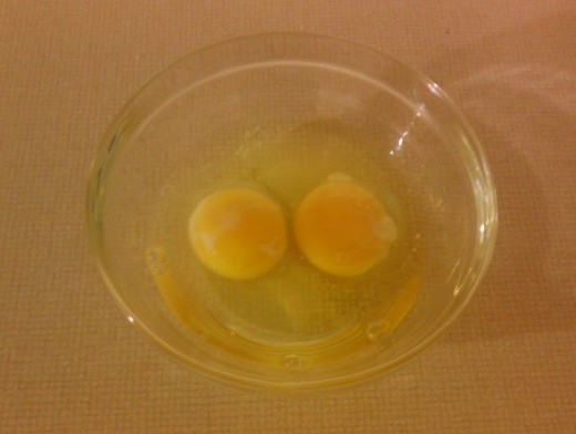 Crack two eggs into a bowl, and beat them slightly.