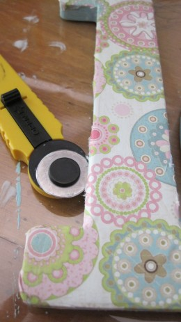 Use a utility blade to trim the paper to mold to the letter.
