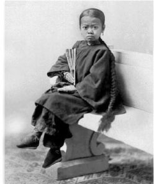 Child waiting to be bought by a new master in the late 1800s.