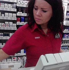 A cashier is human too. This attractive cashier is a single gal with a heavy date later when she gets off work. You can see in her face just how dedicated she is to doing a good job.