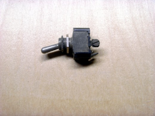 A small toggle switch, commonly found in automotive uses.  The two nuts are used to mount it through sheet metal.