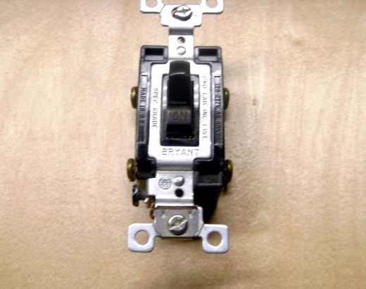 A four way switch, used in conjunction with 2 three way switches to control lighting from multiple locations.  There are four terminals to attach wires to, although none of them get a line wire.