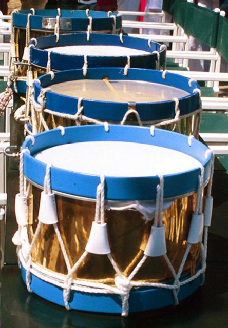 Drums are set on a table while their owners enjoy refreshment.