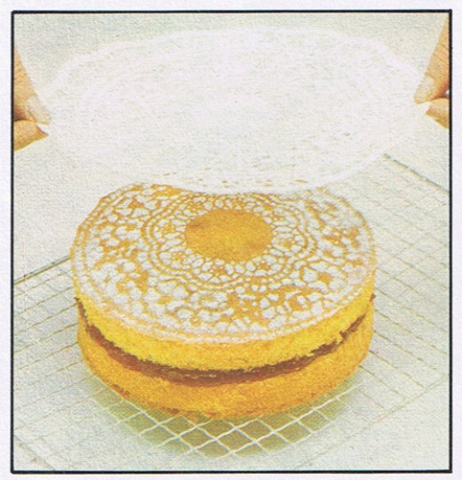 Gently lift the doily off the cake with the tips of your fingers