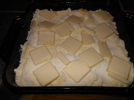 Place thin slices of butter on the cake mix and sugar. Try to spread out evenly. This calls for only half a stick of unsalted butter.