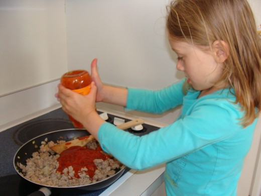 Grace carefully pours the sauce into the pan with the cooked ground turkey.