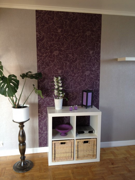 A simple piece of furniture in front of a feature wallpaper.