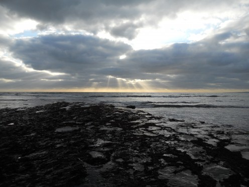 A sunburst breaks through the clouds at Kimmeridge Bay in Dorset