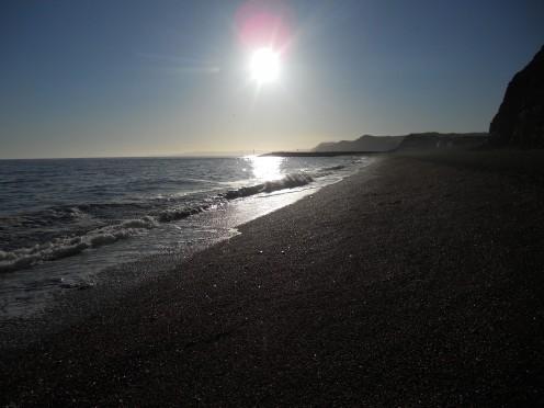 Strong sunlight throws the beach into shadow. West Bay, Bridport, Dorset