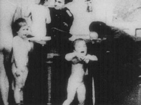 """Children being undressed in preparation for the :showers"""" they were supposed to take before being assigned to a barracks.   After the """"shower"""" the bodies were removed from the gas chamber and cremated."""