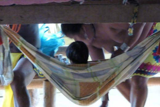 A topless Embera mother checking on her child in a hammock under one of the craft tables.