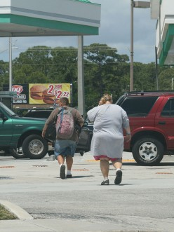"""Coincidence or planned? Two overweight people """"walking"""" toward a restaurant that features low-priced specials."""