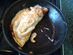 Omelet folded in half.  This is sufficiently cooked for a pale omelette. Otherwise cook it half a minute longer to brown it