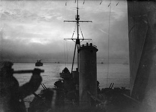 HMS Sheffied as she sails in an Arctic convoy- keeping a steady watch on the merchant ships behind her