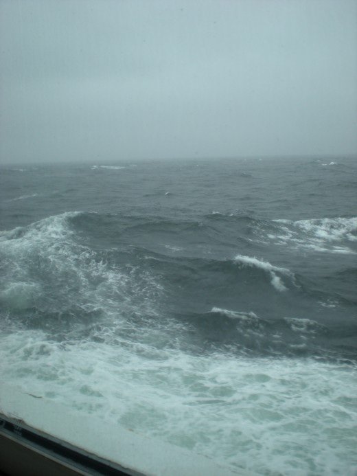 In the Alaska Inside Passage in late August, the Celebrity Mercury wake foams white on the gray sea.