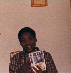 Reggie (1980) holding  'Bible Readings for the Home' book