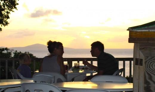Romantic sunsets happen every night on St. John. A couple enjoys dinner as the sun dips below the horizon