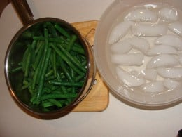 Place the steamed beans into an ice bath to stop the cooking.  Leave it in for just a few seconds and remove.