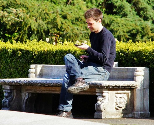 A single, good-looking guy just sitting alone in the park texting his dad because he has no girlfriend to burn up his cellphone minutes.