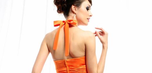 A woman wearing a modern orange dress.