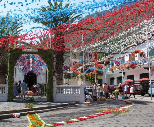 A flower carpet is laid on the street through the village