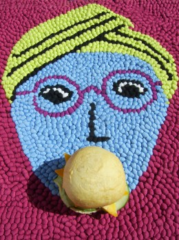 A BUN IN THE MOUTH by Iamablever  A blue, crocheted face on a stool cover with a hamburger bun placed in the mouth