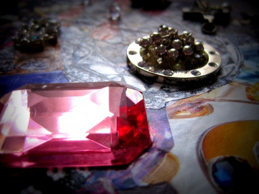 Detail of pink gem and pile of silver beads.