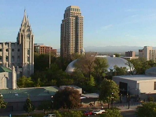 A view overlooking part of Temple Square including the famous Salt Lake Tabernacle with its domed roof,  and The Assembly Hall's steeple in Salt Lake City, Utah.  The Salt Lake Temple is partially seen at the left of this photo.