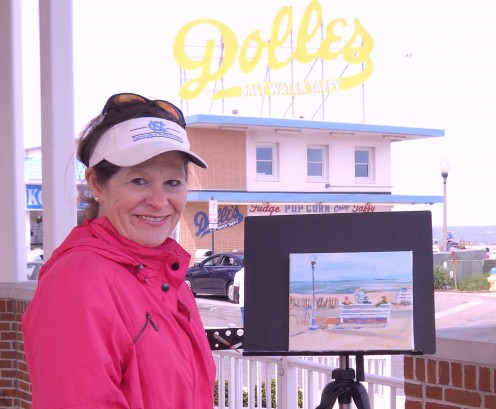Christine A. Heyse poses in front of her watercolor painting of Rehoboth Beach Boardwalk.