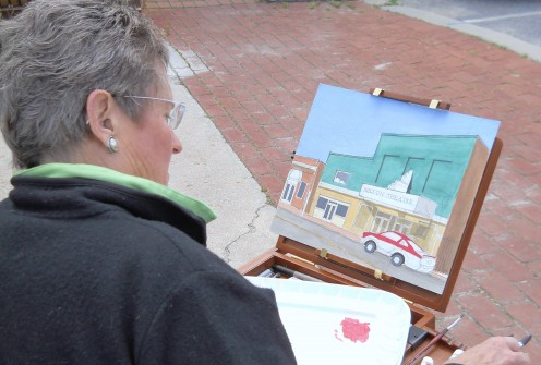 Arlene Matzkin painting the Milton Theatre, capturing a piece of Milton's history for posterity.