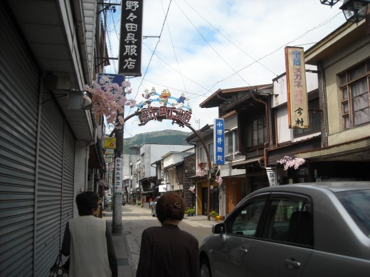 "Old Town Gujo City, with a sign displaying the traditional ""Gujo Odori"" festival."