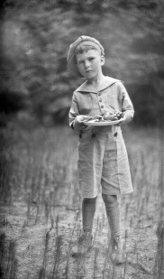 A Little Boy Holding Out His Plate in the 20s