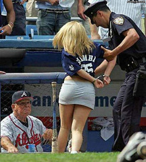 This pretty girl is being arrested for a major crime: Disturbing the male fans of this Atlanta Braves baseball game by wearing a skirt that is too short and tight for public appearances.