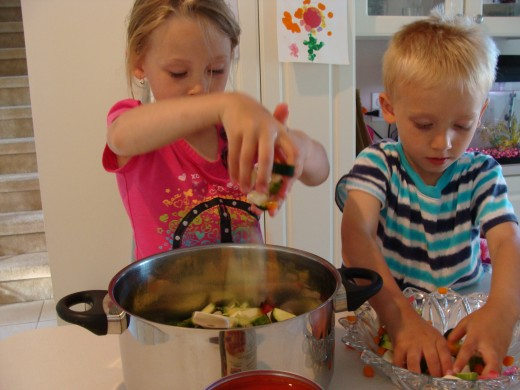 Grace and Alex are having fun putting the vegetables in the pot.