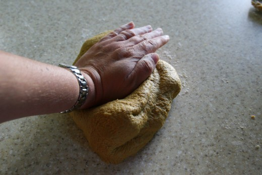 Fold the dough over, rotate by 90 degrees, and press the dough out again.