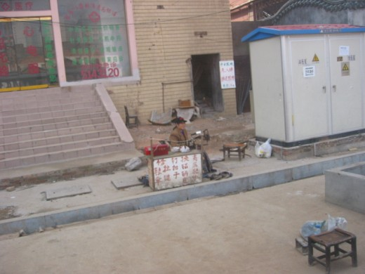 "Chinese Sewing Repair Shop: Here is a man with a sewing business, set up on a side street.  In another area, I saw a long row of ""shoe shine"" men."