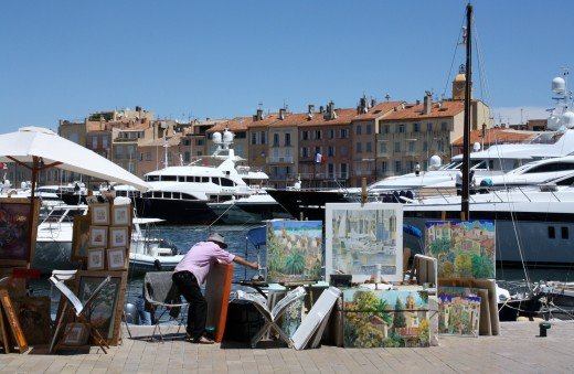 The restaurants of the Quay Juarez is beyond the yachts in the port of St. Tropez. Artisits sell their work in the foreground/