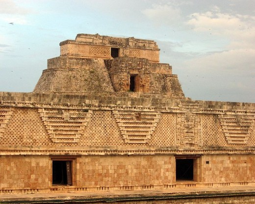 Ancient buildings from the ruined city of Uxmal, Mexico. The short building at the front is the southern construction of the Nunnery Quadrangle and displays the characteristcs of Puuc mayan architecture of the period: the detailed stone mosaic work a