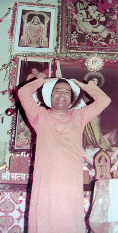 Swami playfully tied a towel to His hair to show how Lord Krishna would do the same when he took the cows out for grazing. In the background there is the picture of Swami on the lotus about which Swami made a special mention in part 2 of this article
