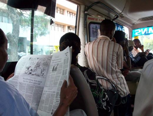 "A man reading the Daily Nation of Kenya inside a Dar-es-Salaam ""Dala dala"" public vehicle"