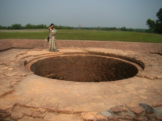 The lady is dwarfed by the size of the well