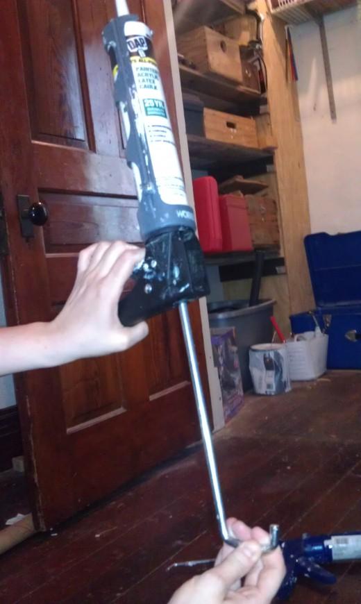 Loading a Caulk gun to prepare for sealing.