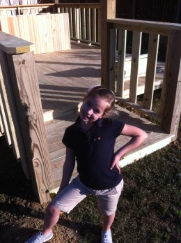 My daughter poses in front of the front porch railings.
