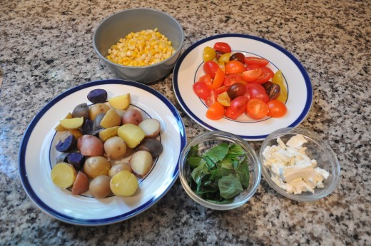 Clockwise , from bottom left. Potatoes, corn, tomatoes, goat cheese, basil.