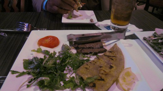 A delectable appetizer is, Balsamic Marinated Steak and Flatbread with roma tomatoes, baby arugula and fresh mozzarella.