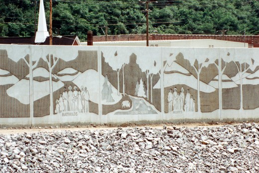 Close-up of a section of the floodwall along the Tug Fork River at Matewan, West Virginia, USA. The U.S. Army Corps of Engineers constructed levees and floodwalls along the river to protect the town. The wall depicts the families involved in the noto