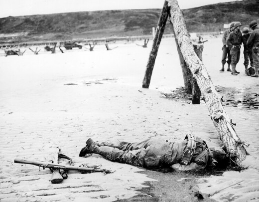 Crossed rifles in the sand are a comrade's tribute to this American soldier who sprang ashore from a landing barge and died at the barricades of Western Europe. 1944
